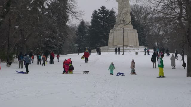 Kids enjoying sleigh ride in a public park in a cold winter day