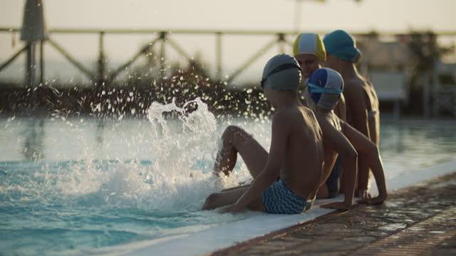 stockvideo's en b-roll-footage met jonge geitjes die van het spetteren in zwembad genieten - 10 11 jaar