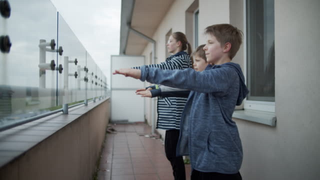 kids exercising at balcony the covid-19 pandemic - crouching stock videos & royalty-free footage