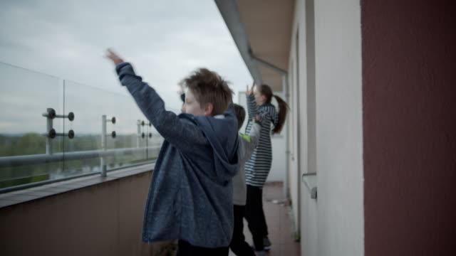 vídeos y material grabado en eventos de stock de niños haciendo ejercicio en el balcón de la pandemia covid-19 - sports training