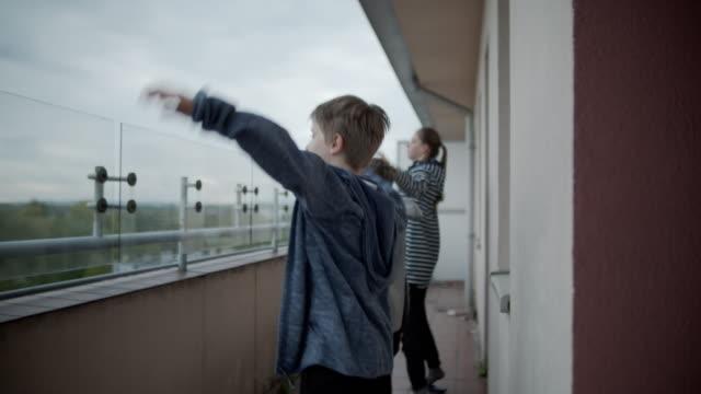 vidéos et rushes de enfants faisant de l'exercice au balcon de la pandémie covid-19 - rester à la maison expression