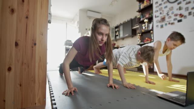vídeos y material grabado en eventos de stock de niños haciendo ejercicio en casa durante la pandemia covid-19 - flexiones