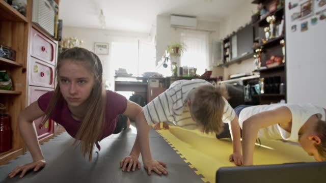 vidéos et rushes de enfants faisant de l'exercice à la maison pendant la pandémie de covid-19 - rester à la maison expression