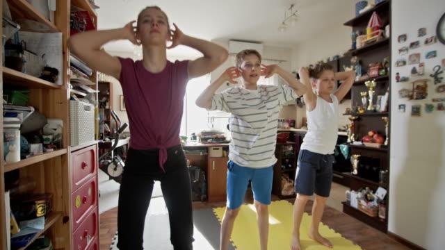 vídeos de stock e filmes b-roll de kids exercising at home during the covid-19 pandemic - isolado