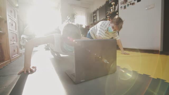 vídeos y material grabado en eventos de stock de niños haciendo ejercicio en casa durante la pandemia covid-19 - sports training