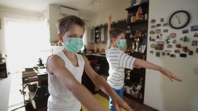 vídeos y material grabado en eventos de stock de niños haciendo ejercicio en casa durante la pandemia covid-19 - orden de permanecer en casa