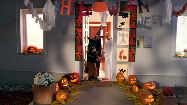 hd crane: kids going trick or treading on halloween - saying goodbye stock videos & royalty-free footage
