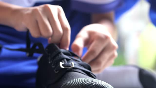 キッズハンズは、自宅の床に黒いキャンバスの靴ひもを結び、学校に行く準備ができています。 - スポーツユニフォーム点の映像素材/bロール