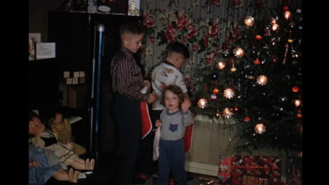 vidéos et rushes de 1957 home movie kids hanging christmas stockings / toronto, canada - nostalgie