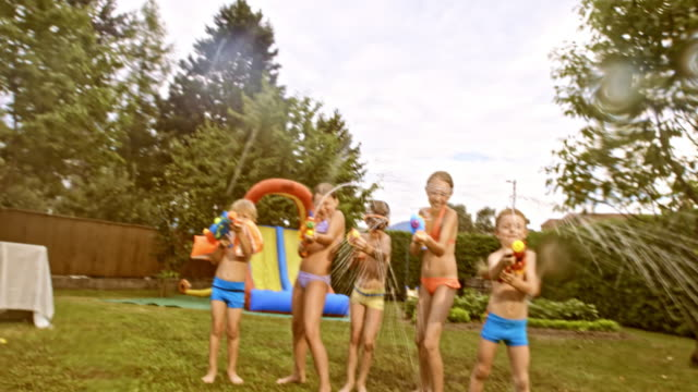 pov kids having a water gun fight at a party in the backyard - squirt gun stock videos and b-roll footage
