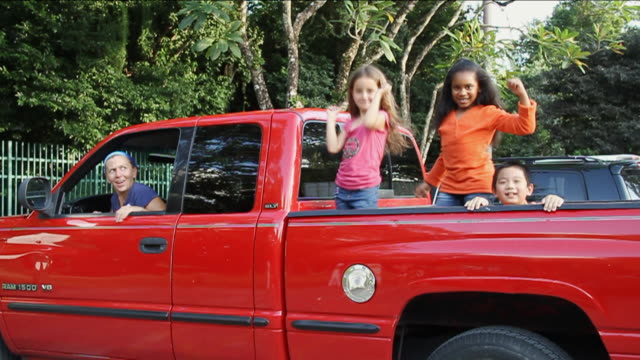 MS Kids having fun on back of red truck / Miami, Florida, United States