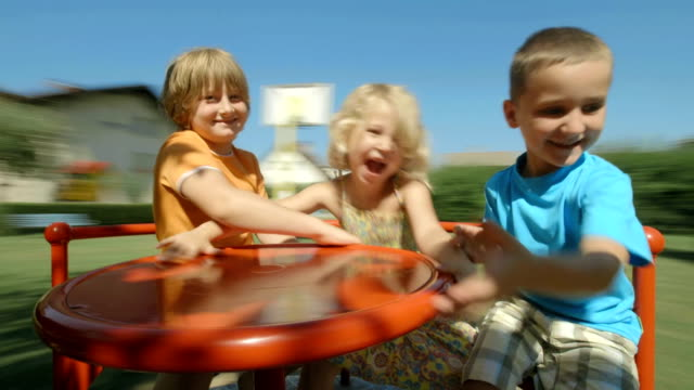 hd: bambini divertirsi su carosello - parco giochi video stock e b–roll