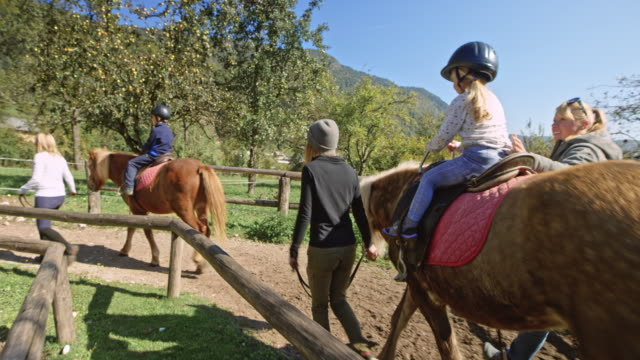 kids having fun riding on horses in sunshine - ranch stock videos & royalty-free footage