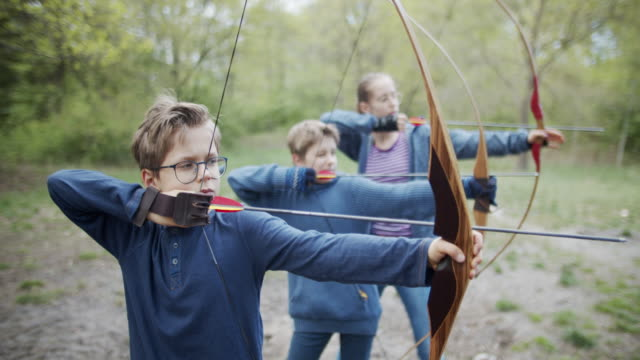 kids having fun shooting bows in the forest - aiming stock videos & royalty-free footage