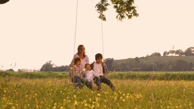 slo mo kids having fun swinging on a rope swing - rope swing stock videos & royalty-free footage