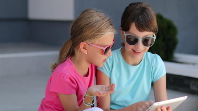 Kids having fun with digital tablet outdoor