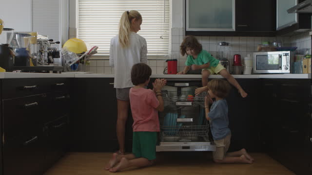 vidéos et rushes de kids helping their mother with dishes and put them in a dishwasher - lave vaisselle