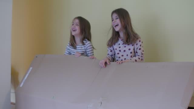 kids hiding in cardboard box, handheld shot - hide and seek stock videos and b-roll footage