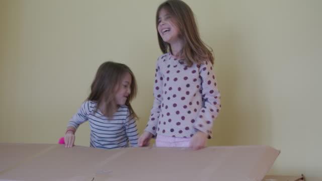 kids hiding in cardboard box, handheld shot - cardboard box stock videos & royalty-free footage