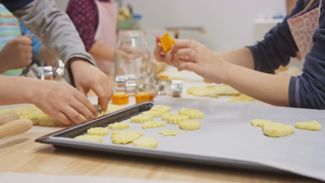 kids in a cookie making workshop placing cookies onto the baking tray - biscuit stock videos and b-roll footage