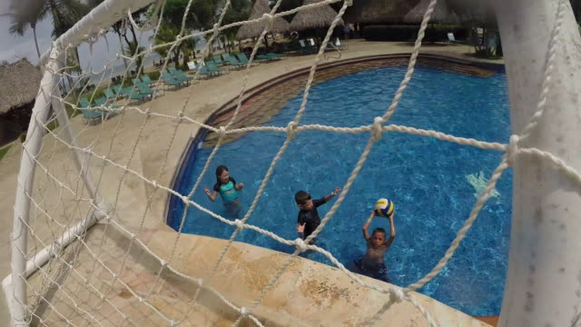 kids in pool playing basketball throw ball into net at resort. - kelly mason videos stock-videos und b-roll-filmmaterial
