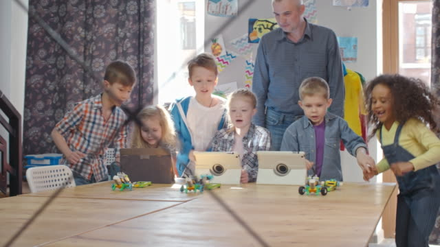 kids joyous about playing with programmable robots - klassrum bildbanksvideor och videomaterial från bakom kulisserna