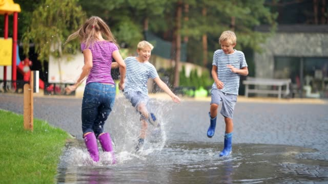 kids jumping and splashing in rain puddle - boot stock videos & royalty-free footage