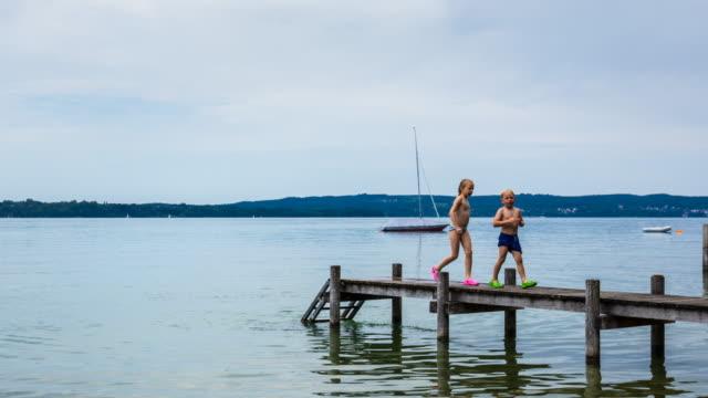 tl kids jumping from pier into lake - nackter oberkörper stock-videos und b-roll-filmmaterial