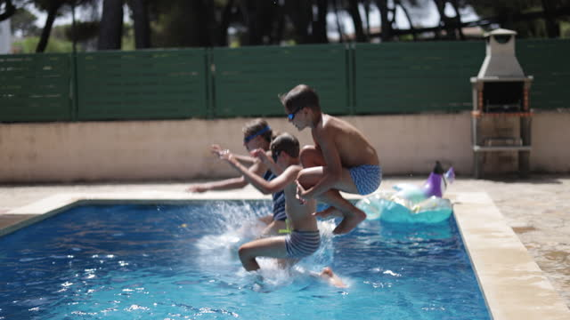 kids jumping into swimming pool on summer day. - vanliga människor bildbanksvideor och videomaterial från bakom kulisserna