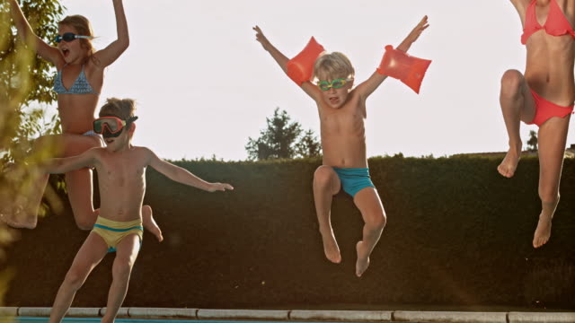 slo mo ds kids jumping into the pool at sunset - jumping stock videos & royalty-free footage