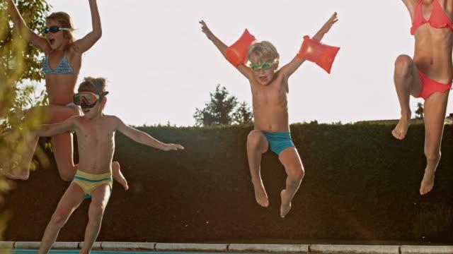 vídeos y material grabado en eventos de stock de cámara lenta ds niños salto en piscina al anochecer - vista de frente