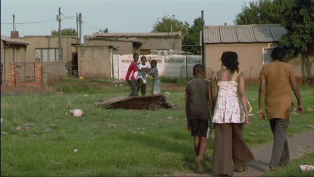 ws kids jumping on mat in yard / south africa - hand an der hüfte stock-videos und b-roll-filmmaterial