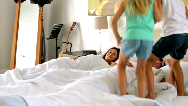dolly: kids jumping on parents bed - waking up stock videos & royalty-free footage