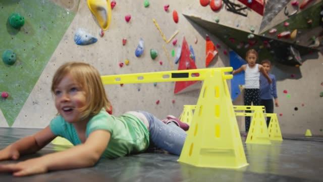 stockvideo's en b-roll-footage met ld kinderen springen over en kruipen onder de kleine hindernissen op de sportschool - vrij klimmen