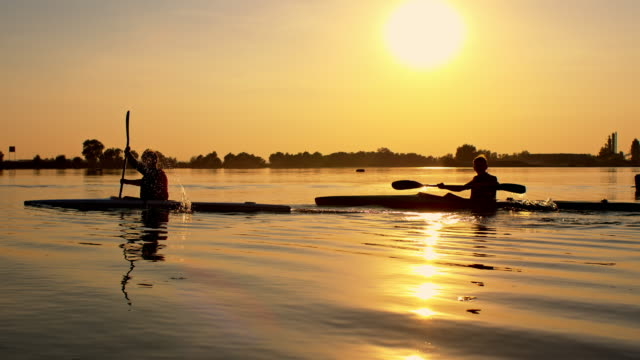 kids kayaking on the lake at sunset - canoe stock videos & royalty-free footage