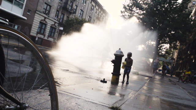 kids keeping cool in a fire hydrant on a brooklyn, new york city street during the summer of 2016. - fire hydrant stock videos & royalty-free footage