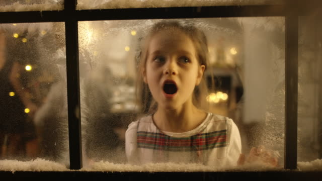 kids looking out of the snowy window - christmas lights stock videos & royalty-free footage