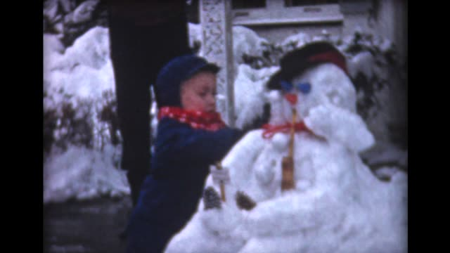 1959 kids make snowman, sit in cart - 1950 1959 stock videos & royalty-free footage