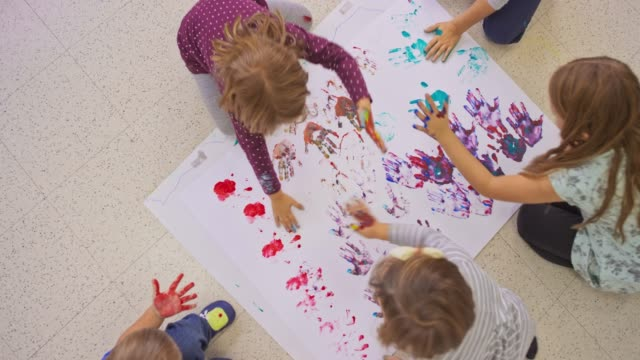kids making handprints onto a white paper on the floor - preschool child stock videos & royalty-free footage