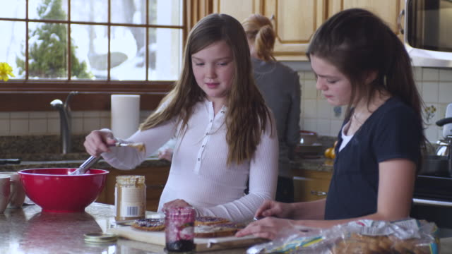 ms tu td kids making sandwich while dad takes it with mother in background / rutland,vermont, usa - サンドイッチ作り点の映像素材/bロール