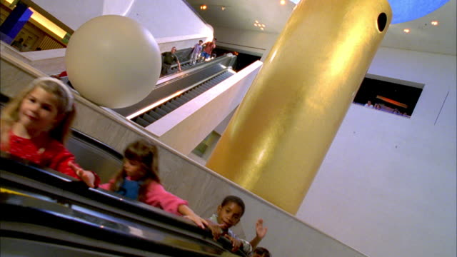 ws kids moving up on escalator and waving hands, smiling / san jose, california, usa - rolltreppe stock-videos und b-roll-filmmaterial