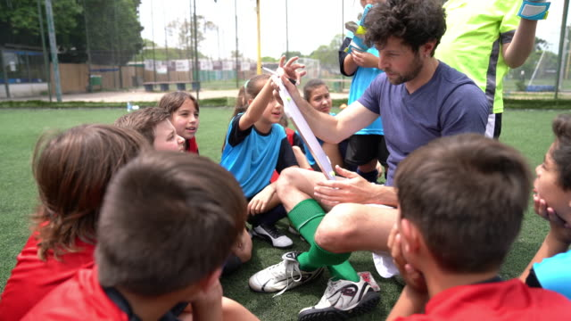 kids of a soccer team listening to their coach, sitting together on a soccer field - ethnicity stock videos & royalty-free footage