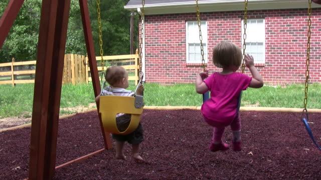 vídeos y material grabado en eventos de stock de niños en un columpio - columpiarse