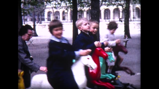 stockvideo's en b-roll-footage met 1965 kids on rocking horses near champs elysees - archief