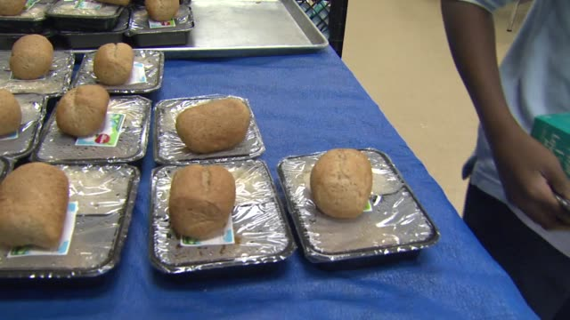 """kids pick up trays of hot lunches with rolls and milk. signage """"revolution foods fight junk food"""" - school dinner stock videos & royalty-free footage"""