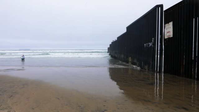 Kids play by the USMexico border fence which runs up to the ocean on March 9 2018 in Tijuana Mexico