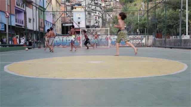 vídeos de stock e filmes b-roll de ws, tu kids play football in a favela / rio de janeiro, brazil - favela