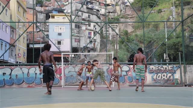 vídeos de stock e filmes b-roll de ms kids play football in a favela / rio de janeiro, brazil - favela