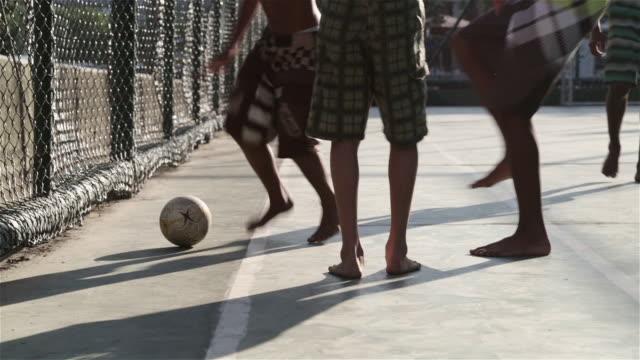 """cu, pan kids play football in a favela / rio de janeiro, brazil"" - barfuß stock-videos und b-roll-filmmaterial"