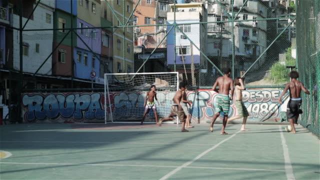 vídeos de stock e filmes b-roll de ws kids play football in a favela / rio de janeiro, brazil - favela